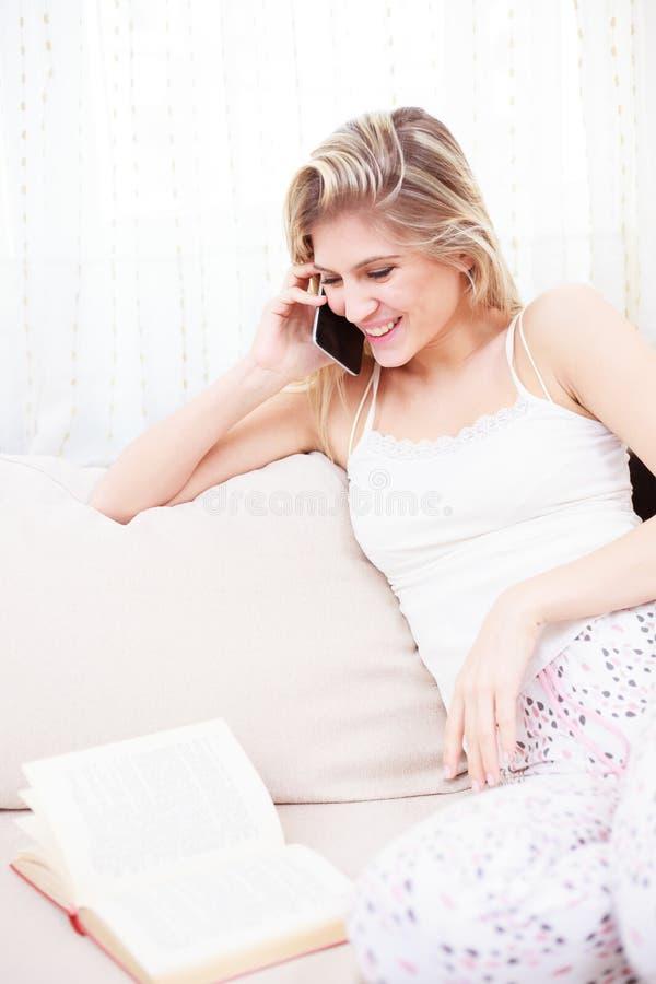 Mooie glimlachende jonge vrouw die op de telefoon spreken stock foto
