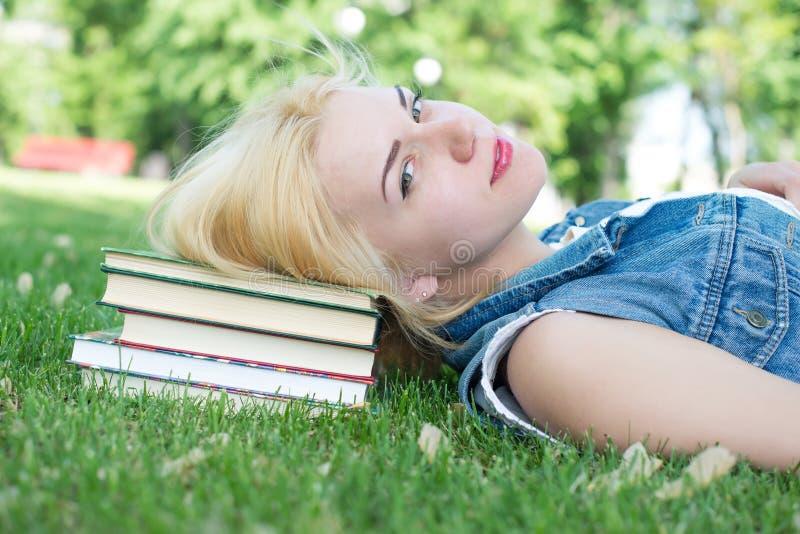 Mooie glimlachende jonge vrouw die op gras liggen stock afbeelding