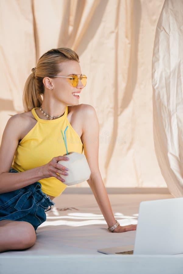 mooie glimlachende jonge vrouw die in zonnebril de cocktail van de de zomerkokosnoot houden royalty-vrije stock fotografie