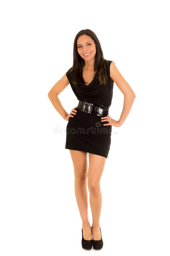 Mooie glimlachende jonge vrouw, dragend een zwarte kleding en stellend voor camera, op een witte achtergrond royalty-vrije stock afbeelding