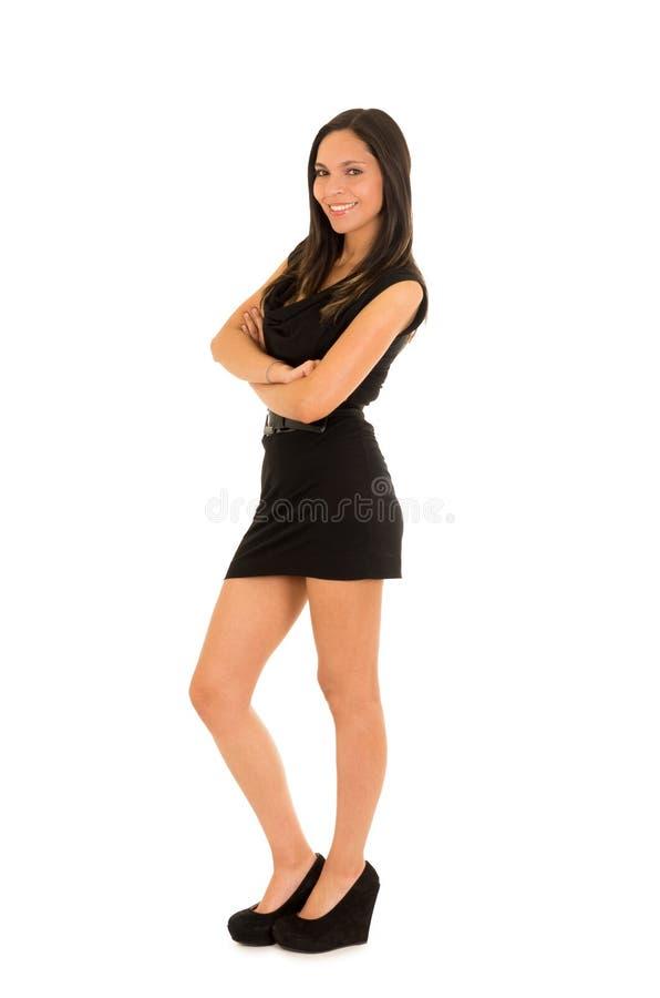 Mooie glimlachende jonge vrouw, dragend een zwarte kleding en stellend voor camera, op een witte achtergrond stock fotografie