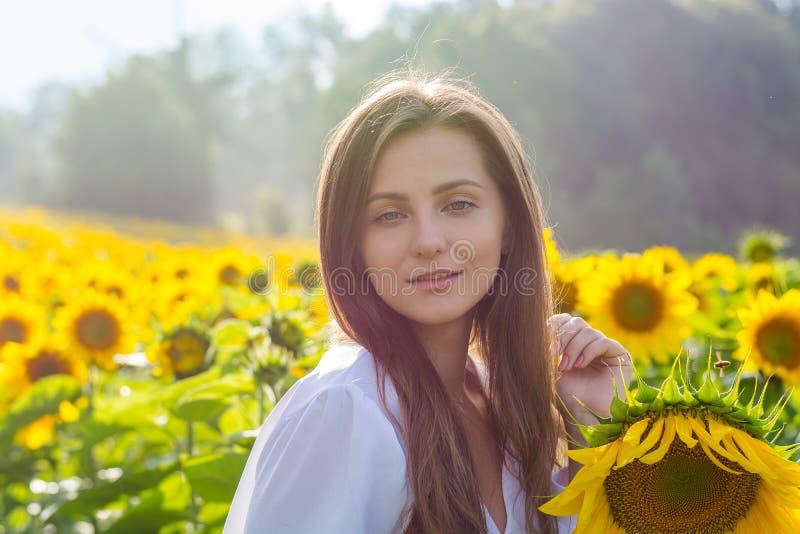 Mooie glimlachende jonge vrouw in een witte overhemdstribunes in fie royalty-vrije stock afbeeldingen