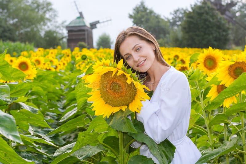 Mooie glimlachende jonge vrouw in een witte overhemdstribunes in fie royalty-vrije stock foto's