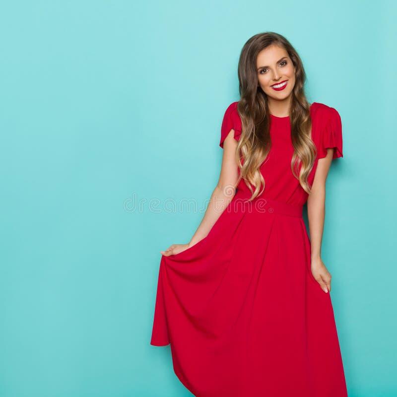 Mooie Glimlachende Jonge Vrouw in Lange Rode Kleding stock afbeelding