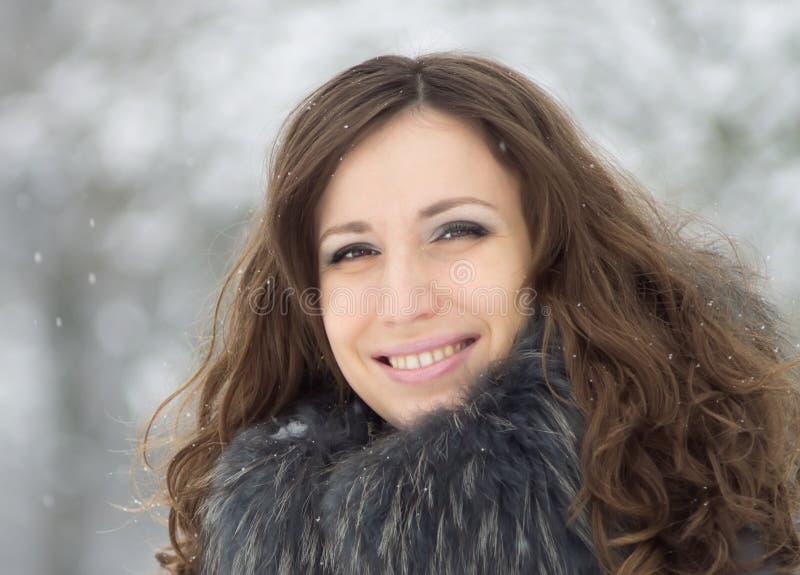Mooie glimlachende jonge vrouwen in sneeuw de winterpark stock foto