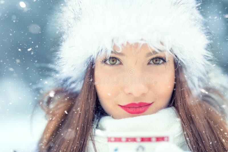 Mooie glimlachende jonge vrouw in warme kleding met kop van hete theekoffie of stempel Het concept portret in de winter sneeuwwea royalty-vrije stock afbeelding