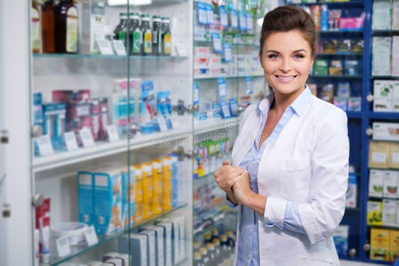 Mooie glimlachende jonge vrouwenapotheker die zijn werk in apotheek doen stock afbeeldingen