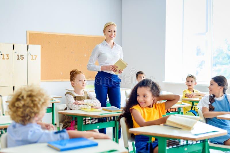 mooie glimlachende leraar die door klaslokaalhoogtepunt lopen van stock foto