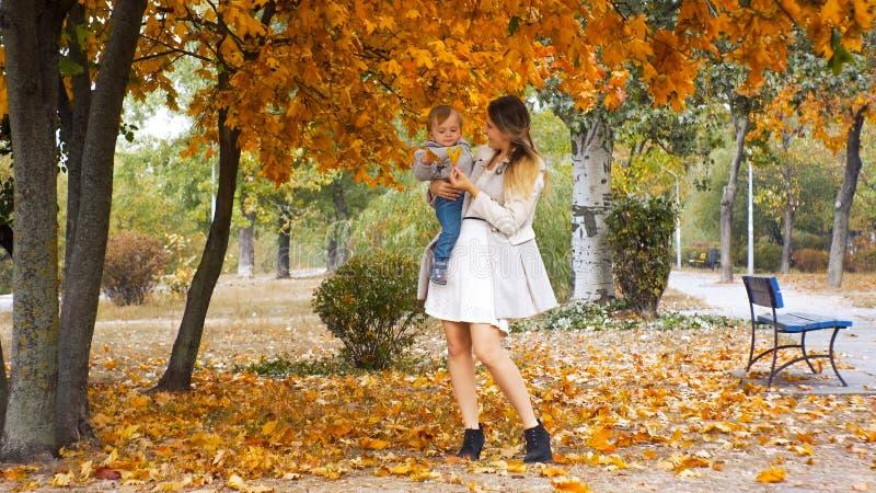 Mooie glimlachende moeder die geel blad van boom geven bij park stock fotografie