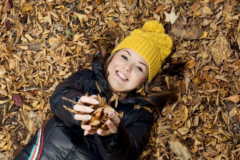 Mooie glimlachende tiener die in de de herfstbladeren liggen stock afbeeldingen