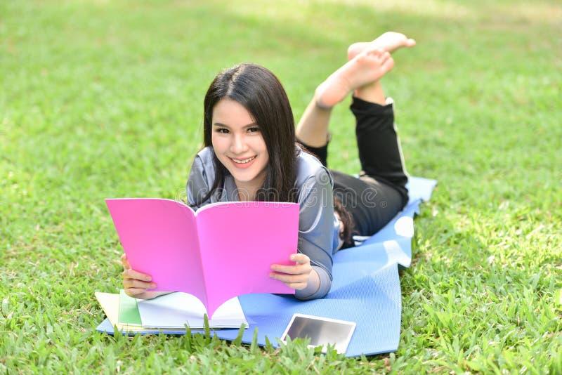 Mooie glimlachende tiener die op gras en gelezen boek liggen royalty-vrije stock afbeeldingen