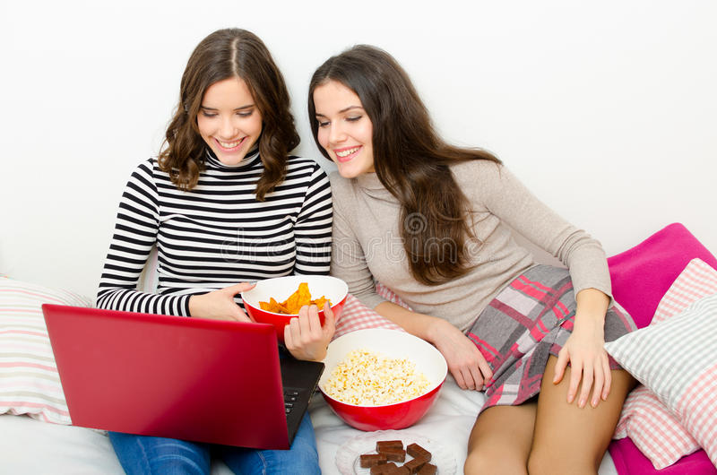 Mooie glimlachende tieners die op films op notitieboekje letten royalty-vrije stock afbeeldingen