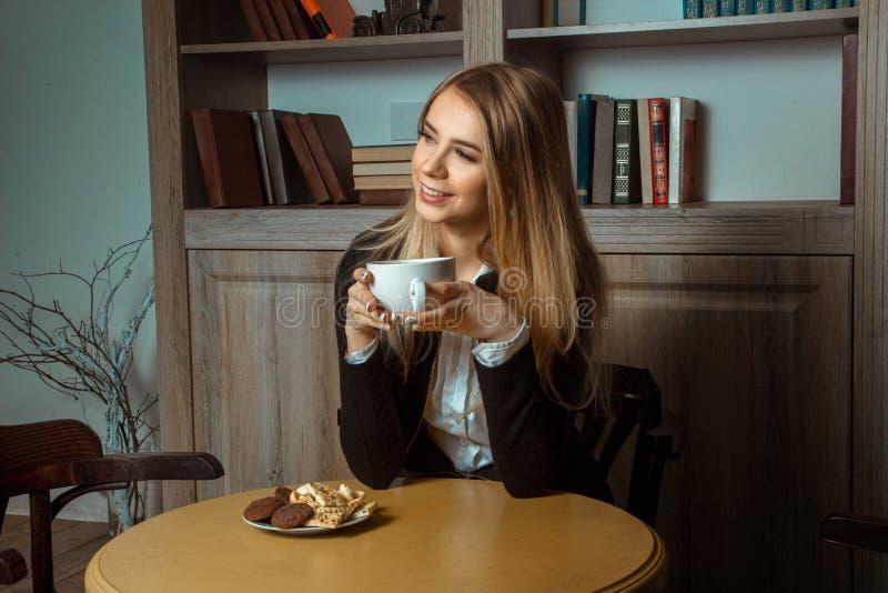Mooie glimlachende vrouw bij een lijst met een kop in zijn handen stock afbeelding