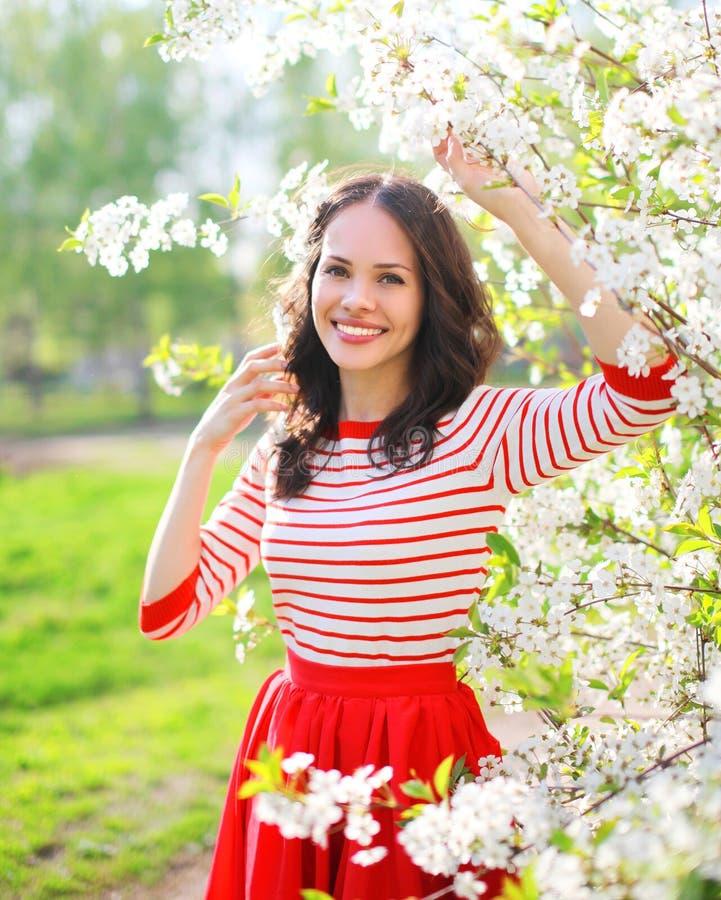 Mooie glimlachende vrouw in bloeiende de lentetuin royalty-vrije stock fotografie
