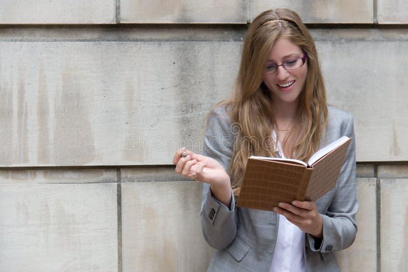 Mooie, glimlachende vrouw die in haar dagboek schrijven royalty-vrije stock foto