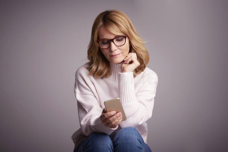 Mooie glimlachende vrouw die haar mobiele telefoon en tekstberichten gebruiken stock foto