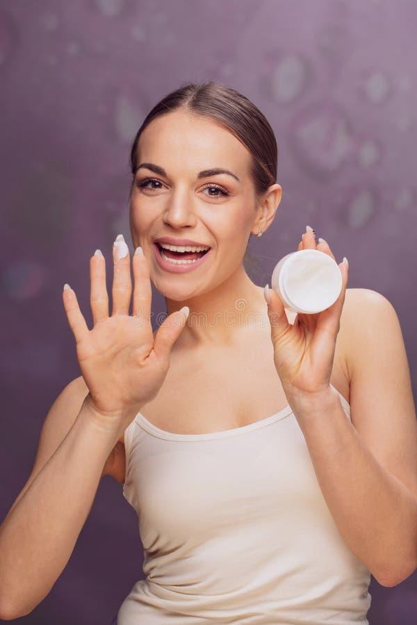 Mooie glimlachende vrouw die kosmetische roombehandeling op haar toepassen royalty-vrije stock foto's