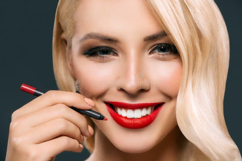 mooie glimlachende vrouw die rode lippen met kosmetisch potlood maken, stock foto's