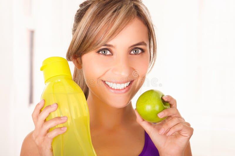 Mooie glimlachende vrouw een purpere t-shirt dragen en een gele fles water houden en een groene appel die in haar andere stock afbeelding
