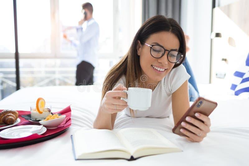 Mooie glimlachende vrouw gebruikend haar mobiele telefoon en drinkend koffie terwijl het liggen op bed in hotelruimte royalty-vrije stock fotografie