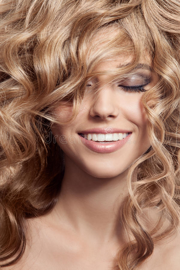 Mooie Glimlachende Vrouw. Gezond Lang Krullend Haar stock afbeeldingen