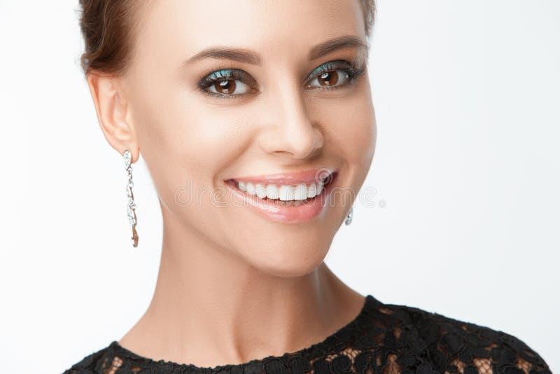 Mooie glimlachende vrouw met avondsamenstelling Juwelen en Schoonheid De foto van de manier royalty-vrije stock afbeelding