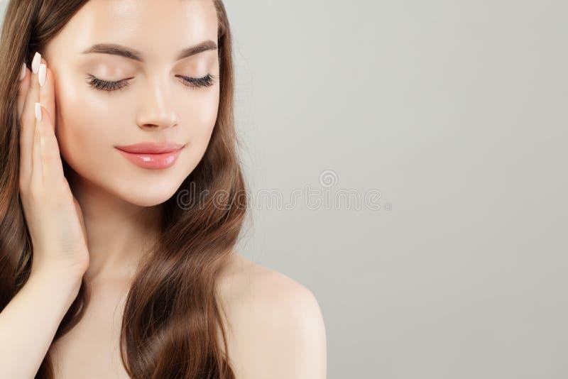 Mooie glimlachende vrouw met duidelijke huid op grijze bannerachtergrond royalty-vrije stock afbeelding