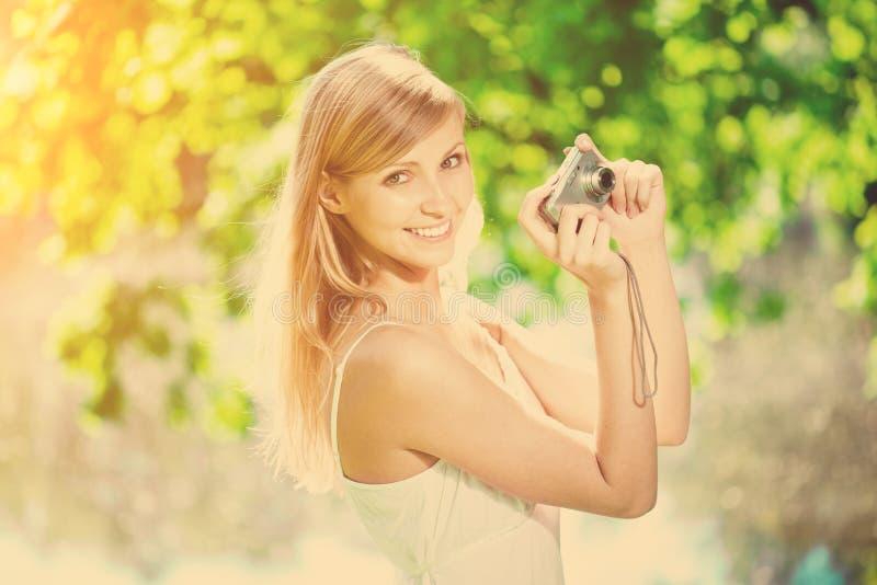 Mooie glimlachende vrouw met een camera, in openlucht royalty-vrije stock fotografie