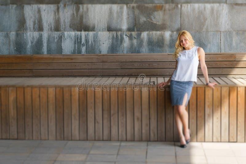 Mooie glimlachende vrouw met golvend blondehaar die in openlucht stellen royalty-vrije stock foto
