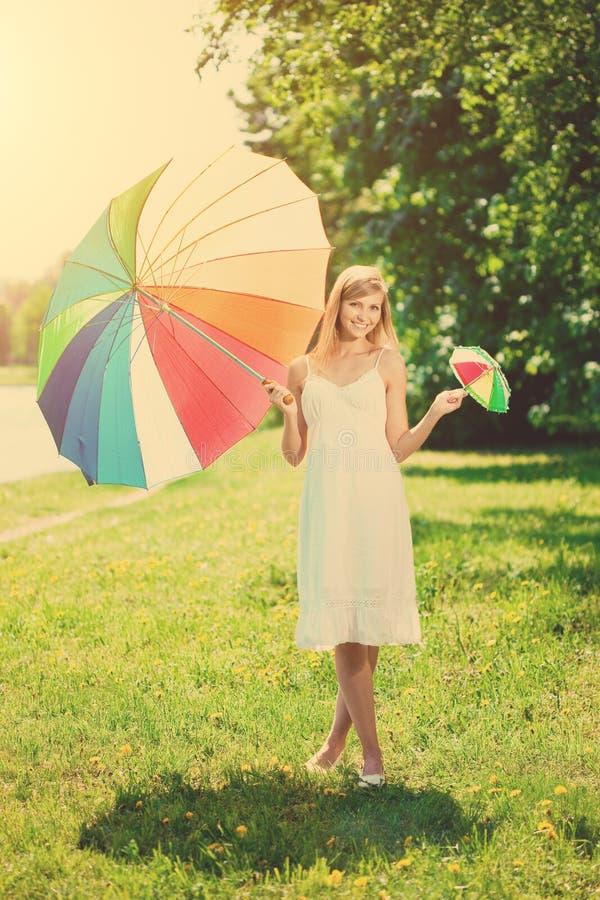 Mooie glimlachende vrouw met twee regenboogparaplu's, in openlucht stock foto