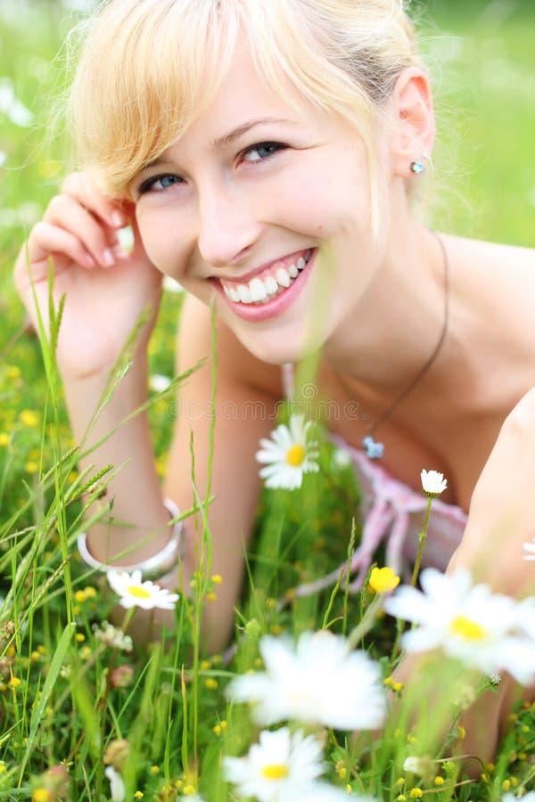Mooie glimlachende vrouw onder de lentebloemen royalty-vrije stock fotografie