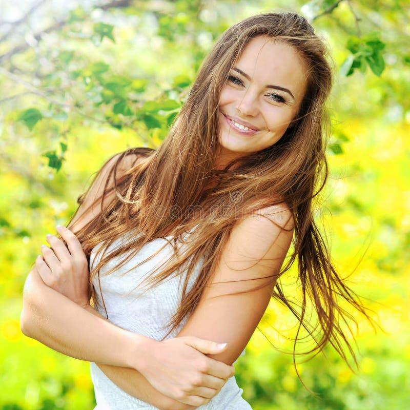 Mooie glimlachende vrouw op aardachtergrond stock afbeelding