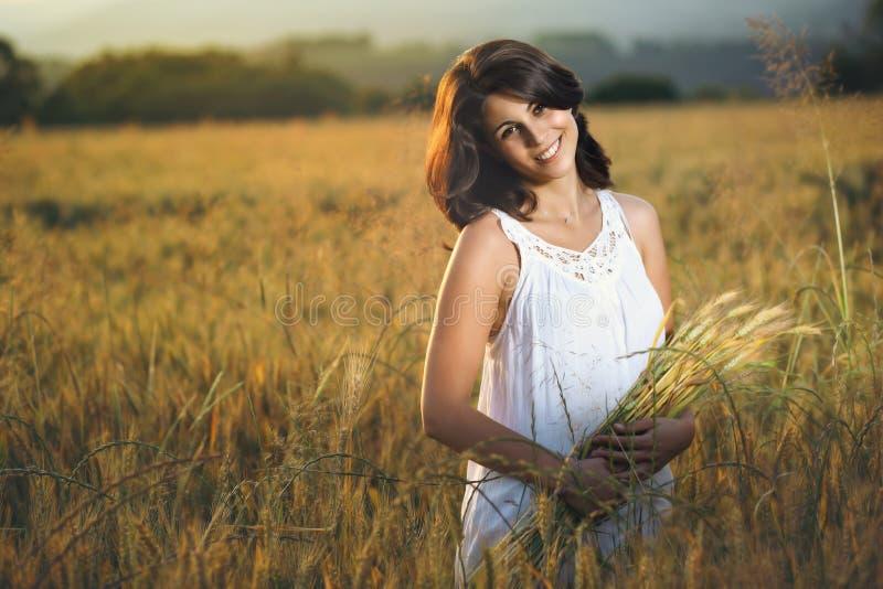 Mooie glimlachende vrouw op een gouden gebied stock afbeeldingen