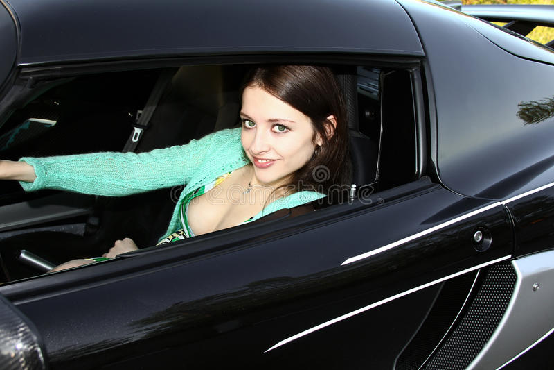 Mooie glimlachende vrouw in sportwagen royalty-vrije stock afbeelding