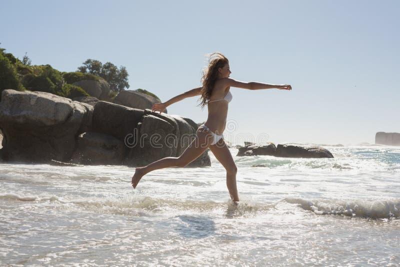 Mooie glimlachende vrouw in witte bikini die op het strand springen stock afbeelding