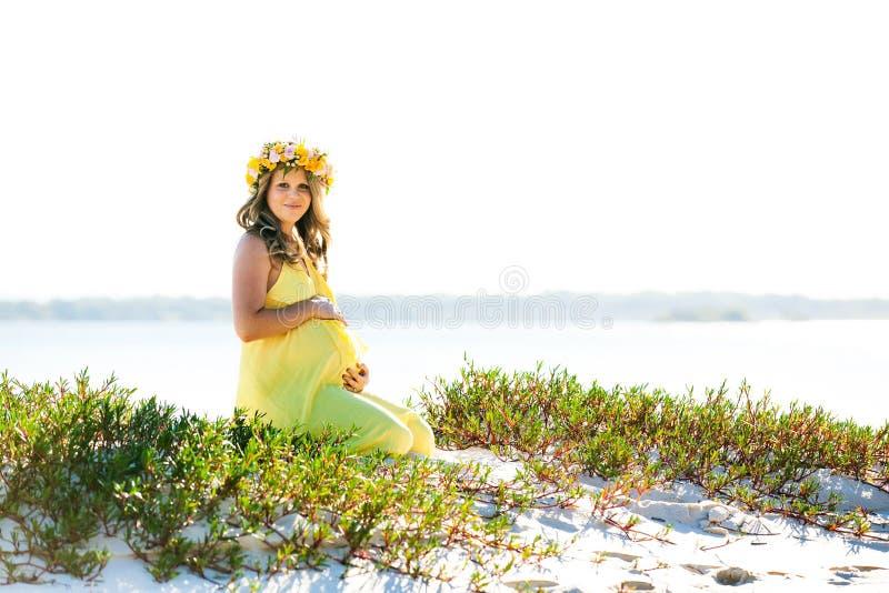 Mooie glimlachende zwangere vrouw die met bloemen op een strand zitten stock afbeelding