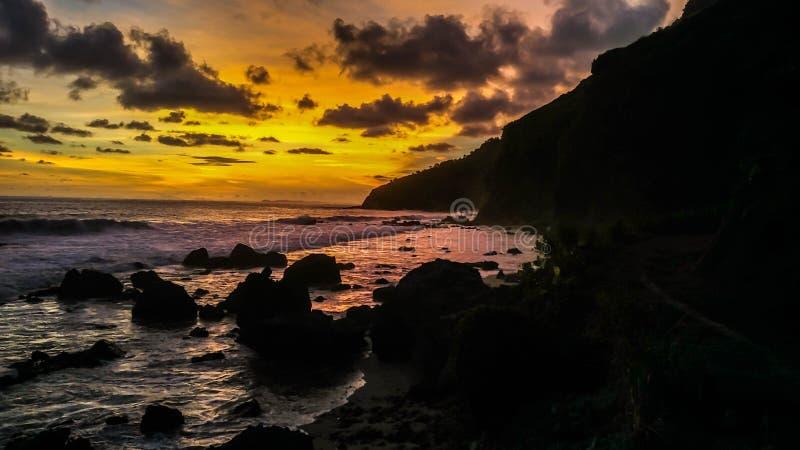 Mooie golvenzonsondergang in Menganti-Strand, Kebumen, Centraal Java, Indonesië stock foto