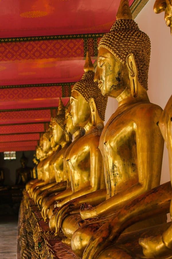 Mooie gouden Boedha op het voetstuk, sommige witte muren stock afbeelding