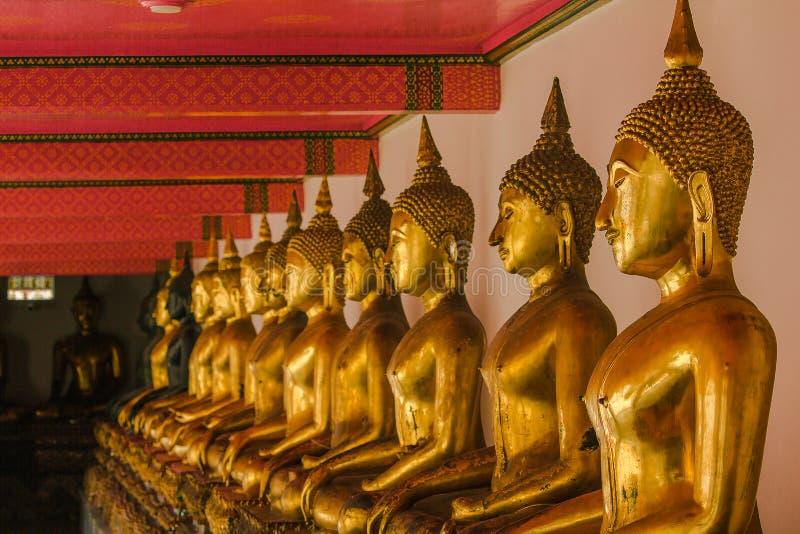 Mooie gouden Boedha op het voetstuk, sommige witte muren stock fotografie