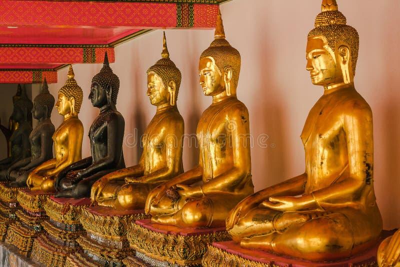 Mooie gouden Boedha op het voetstuk, sommige witte muren stock afbeeldingen