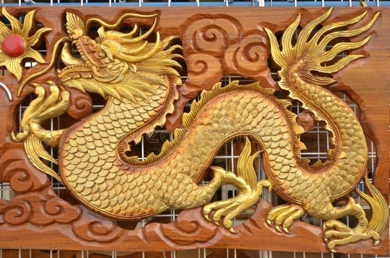 Mooie gouden craven beeldhouwwerk van draak stock afbeelding