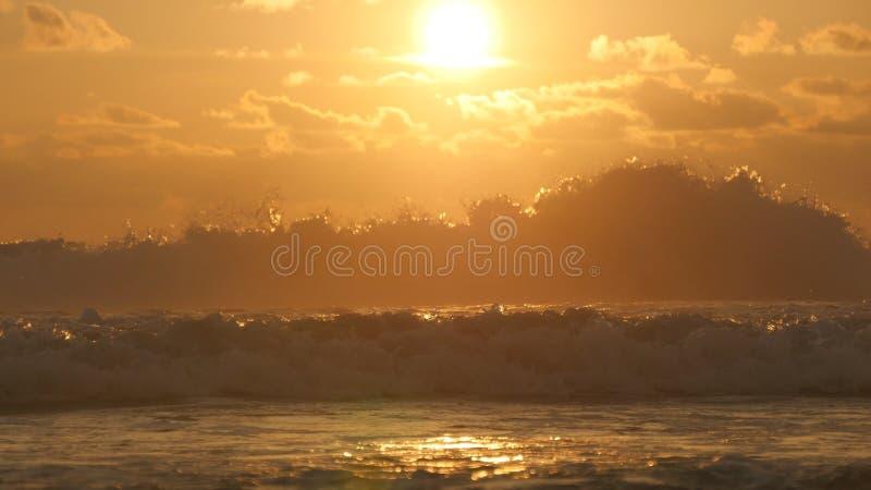 Mooie gouden oceaangolven op zonsondergang Oranje die zonsopgang bij het zeewater wordt weerspiegeld Sterk getijde met golvenplon royalty-vrije stock fotografie