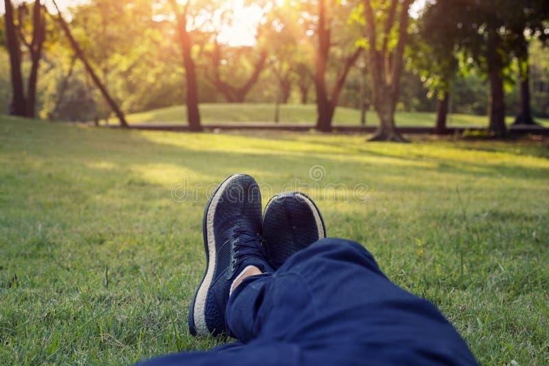 Mooie groene bladerenachtergrond Mannelijke voeten in gumshoes op groen gras in het park bij zonsondergang stock fotografie