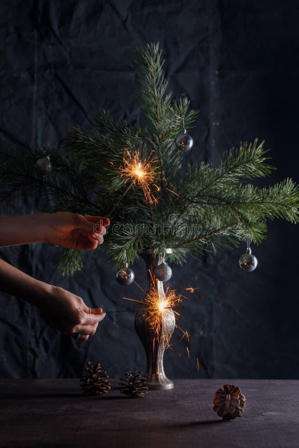 Mooie groetkaart met sterretjes De sterretjes van de handengreep tegen de achtergrond van een verfraaide kleine Kerstboom royalty-vrije stock afbeeldingen