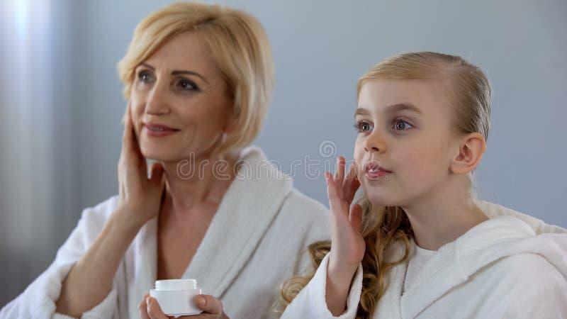 Mooie grootmoeder en kleindochter die gezichtsroom toepassen en, huidzorg glimlachen stock afbeeldingen