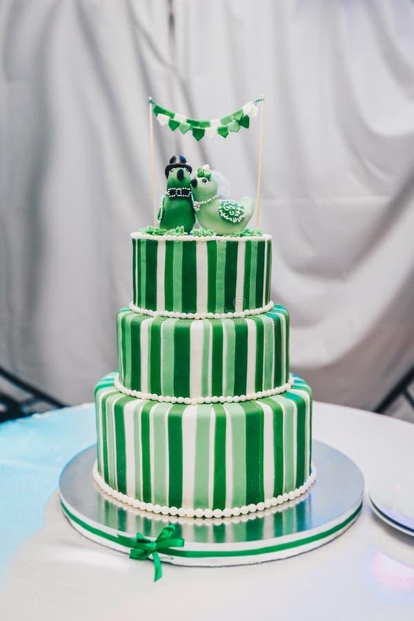 Mooie grote die drie nivelleerden huwelijkscake met twee vogels op de bovenkant wordt verfraaid Een groen-witte gestreepte huweli stock fotografie