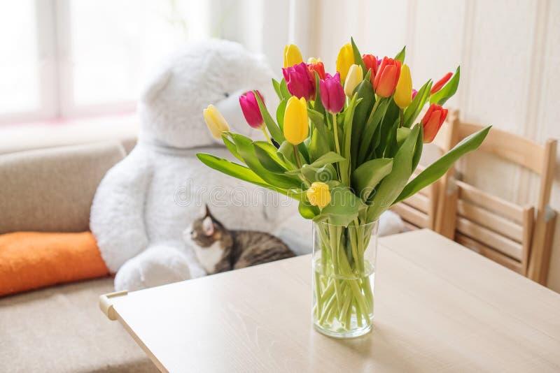 Mooie grote multi-colored tulpen geeloranje en rood in een glasvaas op een lijst tegen de achtergrond van een venster en a royalty-vrije stock foto's