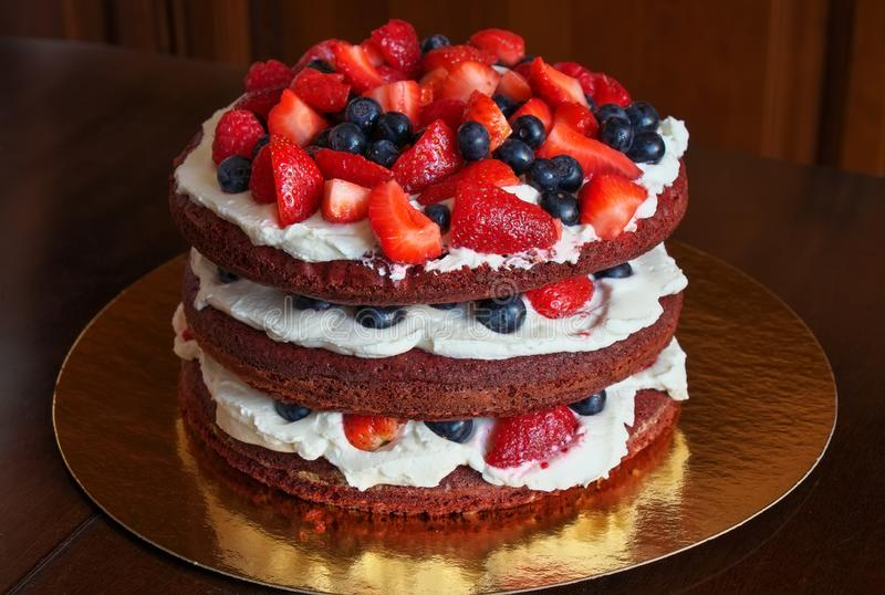 Mooie heerlijke rode fluweelcake met aardbeien en bosbessen stock afbeeldingen
