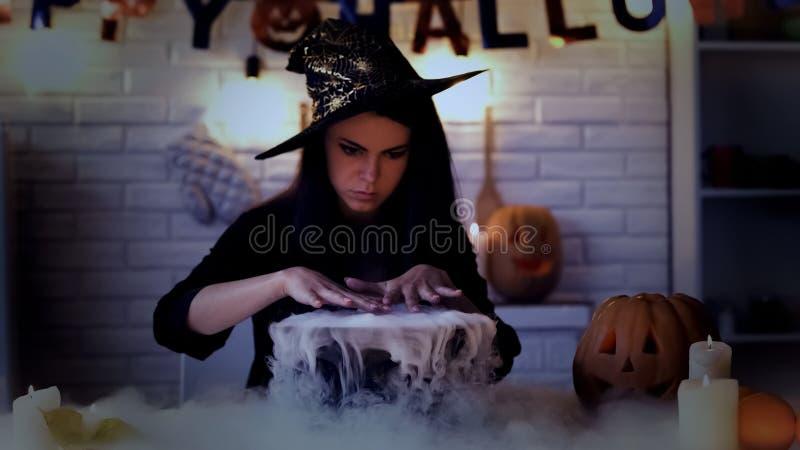 Mooie heks die geheimzinnig magisch ritueel, kokend drankje in ketel uitvoeren stock foto's