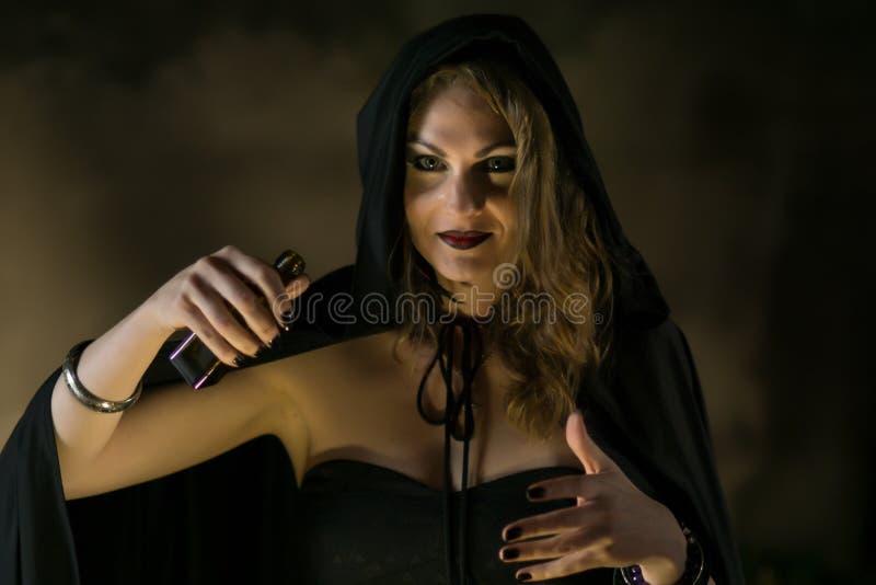 Mooie heks in zwarte mantel op Halloween stock afbeelding